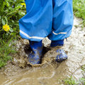 Muddy water puddle child in boots jumping in after rain in the garden Stock Photo