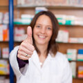 Muestra femenina confiada de showing thumbs up del farmacéutico Fotos de archivo