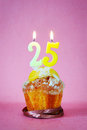 Muffin with burning birthday candles as number twenty five Royalty Free Stock Photo