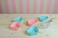 Muffin liners and kitchen wall pink blue egg whisk on wooden surface with pink yellow in background Stock Photo