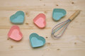 Muffin liners on wooden surface pink and blue and egg whisk kitchen Stock Photography