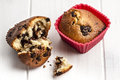 Muffins crumbs wooden table red cupcake case close up shot of delicious chocolate muffin on silicone next to open muffin and on Stock Images