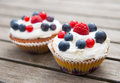Muffins with fruits on wooden board Royalty Free Stock Photo