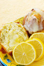 Muffins lemon poppy seed icing sliced lemons forefront yellow textured background Stock Photo