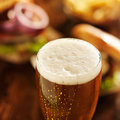 Mug of beer close up at meal photo a with foamy head with hamburgers in the background Stock Photos