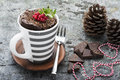A mug cake for a festive New Year`s Eve snack with red white sweets in a striped red white mug on a gray stone