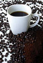 A Mug of Coffee Surrounded by Coffee Beans Royalty Free Stock Photography