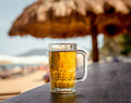 Mug of cold beer with foam on the table against the background the sea the restaurant Royalty Free Stock Image
