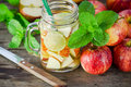 Mug delicious refreshing drink of apple fruits with mint on wooden infused water Stock Images