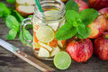 Mug delicious refreshing drink of apple fruits with mint on wooden infused water Stock Image