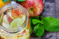 Mug delicious refreshing drink of mix fruits with mint on wooden infused water Royalty Free Stock Image