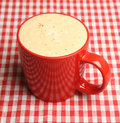 Mug of frothy coffee cappuccino on red checked tablecloth Royalty Free Stock Image