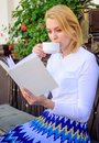 Mug of good coffee and interesting book best combination for perfect weekend. Girl drink coffee every morning same place Royalty Free Stock Photo