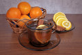 Mug of tea with lemon and cinnamon stick a cup a fragrant wedges tangerines in a wicker basket on a wooden table Stock Photo