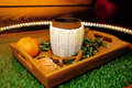 A mug of warm tea with pieces of manadarines on a wooden tray