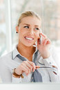 Mujer de negocios rubia hermosa que habla en el teléfono celular mientras que mira el copyspace Imagenes de archivo