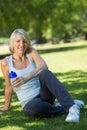 Mujer deportiva que sostiene la botella de agua en parque Fotografía de archivo libre de regalías