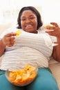 Mujer gorda en casa que come a chips and drinking wine Imagen de archivo libre de regalías