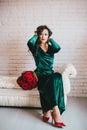 Mujer hermosa en un vestido verde y zapatos rojos con las rosas rojas Imágenes de archivo libres de regalías