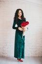 Mujer hermosa en un vestido verde y zapatos rojos con las rosas rojas Fotos de archivo