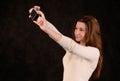 Mujer hermosa joven con la cámara de la foto en las manos que toman una imagen de sí misma en fondo negro Foto de archivo libre de regalías