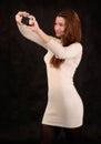 Mujer hermosa joven con la cámara de la foto en las manos que toman una imagen de sí misma en fondo negro Foto de archivo