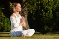 Mujer joven durante la meditación de la yoga en el parque Foto de archivo