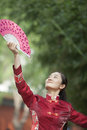 Mujer joven que practica la fan de tai ji with traditional chinese Foto de archivo