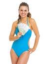 Mujer joven sonriente en el traje de baño que muestra la fan de euros Fotografía de archivo