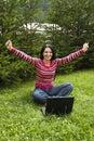 Mujer victoriosa que trabaja en la computadora portátil en vacaciones Fotos de archivo