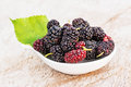 Mulberries with leaf isolated on wood. Royalty Free Stock Photo