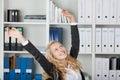 Mulher de negócios with arms raised no escritório Imagem de Stock Royalty Free