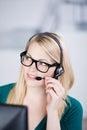 Mulher de negócios nova speaking on headset Imagem de Stock