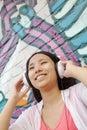 Mulher de sorriso nova que guardara seus auscultadores ao apreciar a escuta a música na frente da parede com grafittis Imagem de Stock Royalty Free