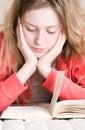 Mulher nova que l� um livro em uma cama Fotografia de Stock Royalty Free