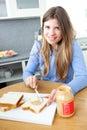 Mulher Relaxed que come o pequeno almoço na cozinha Imagem de Stock Royalty Free