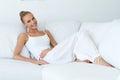 Mulher sexy feliz que inclina se no sofá branco Fotografia de Stock Royalty Free