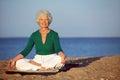 Mulher superior que medita sobre o sandy beach Fotos de Stock Royalty Free