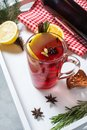 Mulled wine, a bottle of red wine, spruce branches, cinnamon, orange and lemon on white tray on concrete background. Winter drinks Royalty Free Stock Photo
