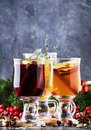 Mulled wine and mulled cider. Hot winter drinks and cocktails for christmas or new year`s eve in glass mugs with spices and citru Royalty Free Stock Photo