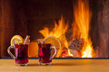 Mulled wine at cozy fireplace in winter with cinnamon and orange slices Royalty Free Stock Photography