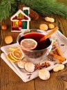Mulled wine in glass with cinnamon stick candle and sweets close up Stock Photo