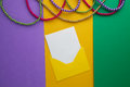 Multi color Mardi Gras beads and envelop with card on paper background. Top view Royalty Free Stock Photo