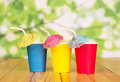 Multi-colored disposable paper cups and straws on abstract green.