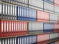 Multi colored folders arranged inside wooden shelves. 3D illustration Royalty Free Stock Photo