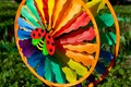 Multi colored round pinwheel in motion, in sunny garden. Big round rainbow pinwheel in motion. Royalty Free Stock Photo