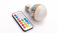 Multi colour led light bulb and remote control with some several colored buttons Royalty Free Stock Photo