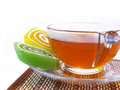 Multi-coloured fruit candy  and cup of hot tea Royalty Free Stock Image