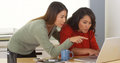 Multi ethnic businesswomen working together to meet deadline in the office Royalty Free Stock Photos