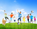 Multi ethnic children outdoors playing soccer together and a pet dog Stock Photography